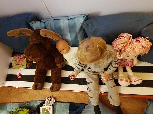 Kleinkind spielt mit Puppen und Kuscheltieren. In der Zeit kann Mama sich etwas vom Alltags-Stress erholen.