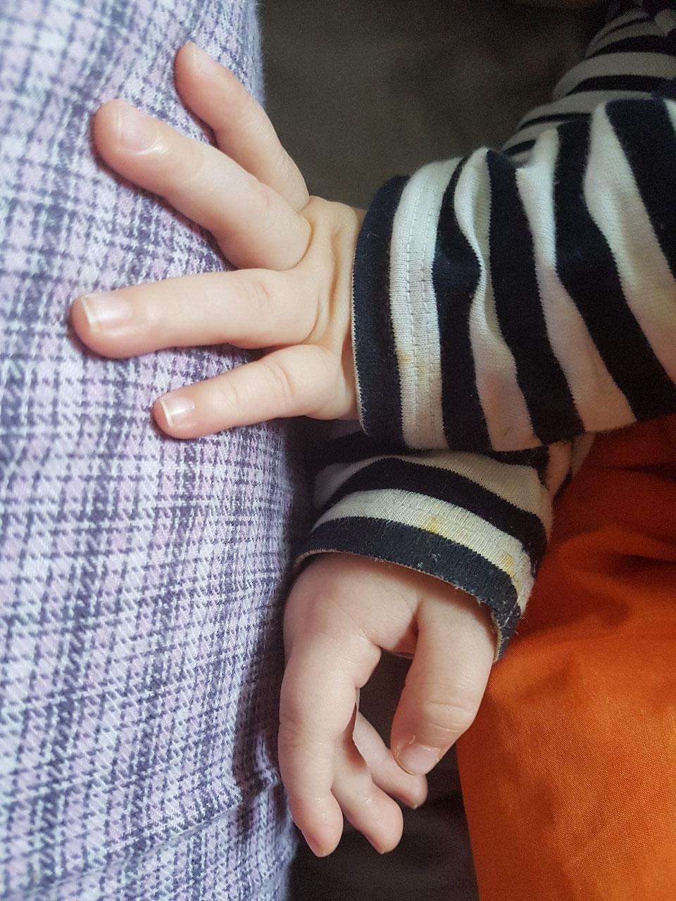 Babyhand berührt das Bein seiner Mama. Symbolbild zum Brief zum ersten Geburtstag auf Mama-Blog Patschehand.de.
